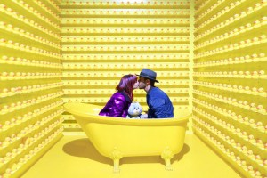 a couple kissing in a yellow bathtub surrounded by rubber ducks