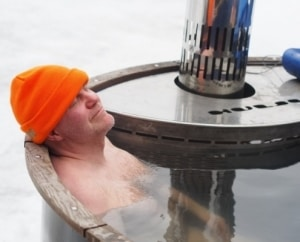 a man laying in an outdoor classic wooden hot tub, relaxed and satisfied